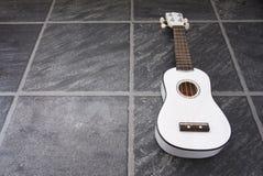 ukulele czarny podłogowy biel Fotografia Royalty Free