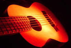 Ukulele della chitarra su luce rossa immagini stock