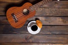 Ukulele delle ukulele con la tazza di caffè ed il croissant immagine stock libera da diritti