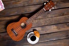 Ukulele delle ukulele con la tazza di caffè ed il croissant fotografie stock