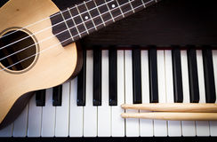 Ukulele with drum sticks on piano. Top view with dark vignette. Concept of music instrument background royalty free stock photo