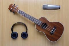 Ukulele e microfono e cuffia sul fondo di legno del pavimento Immagine Stock