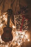 Ukulele Beside a Floral Box and String Lights Royalty Free Stock Photos