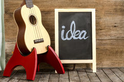 Ukulele guitar and blackboard  with the word  idea  written on wooden background. Royalty Free Stock Photography