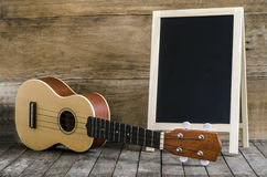 Ukulele guitar and  blank blackboard  on wooden background. Stock Photo