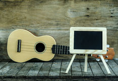 Ukulele guitar and blank blackboard  on wooden background. Royalty Free Stock Images
