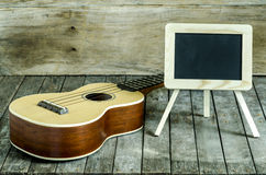 Ukulele guitar and blank blackboard  on wooden background. Stock Photography