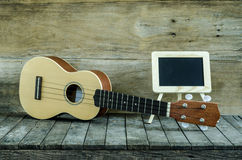 Ukulele guitar and blank blackboard  on wooden background. Royalty Free Stock Image