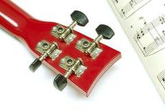 Ukulele Guitar and Music Sheet. Close-up photo of back of ukulele guitar toy and music sheet Stock Images