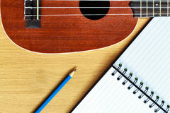 Ukulele guitar with  notebook and pencil Stock Image