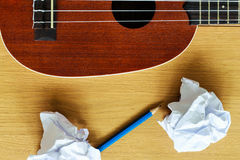 Ukulele guitar with paper scraps and pencil Royalty Free Stock Photos
