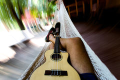 Ukulele and Hammock. Relaxing during the heat of the day in El Salvador. Speed blur shot of ukulele on lap in hammock Stock Photos
