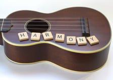 Ukulele-Harmonien mit quadratischen Buchstabe-Fliesen auf Weiß Stockfoto