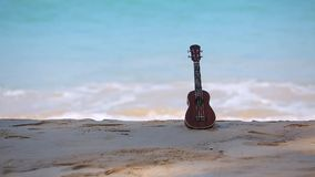 An ukulele, hawai instrument put on the beach and blue sea and wave. Background stock video