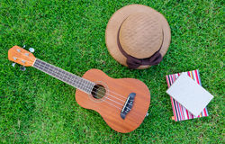 Ukulele lying on meadow with lovely hat and notebook. Royalty Free Stock Photo