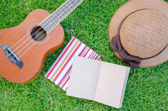 Ukulele lying on meadow with lovely hat and notebook. Royalty Free Stock Photos