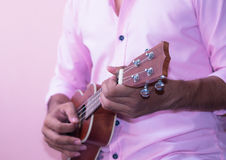 Ukulele. A man wearing pink shirts playing ukulele Royalty Free Stock Photo