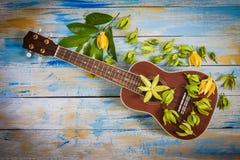 Ukulele mit Ilang-Ilang Blume und Blatt lizenzfreie stockfotos