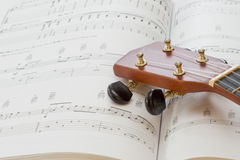 A ukulele and music book. The head of a ukulele resting on a music book Stock Photography