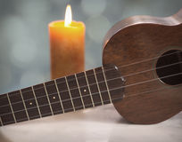 Ukulele Music soft Candle Light with Bokeh Accents. An antique soprano Ukulele in still life sits on a marble table with a brightly lit candle in the background royalty free stock photo
