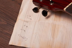 Ukulele and musical paper notes. Ukulele and musical old paper notes on wooden table Royalty Free Stock Photos
