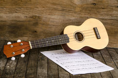 Ukulele and  Paper Chordschart document on wooden background. Stock Photography