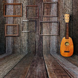 Ukulele and picture frame. In vintage wood room Royalty Free Stock Photography