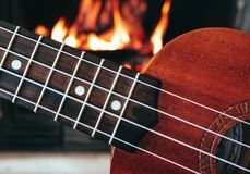 Ukulele small guitar close up stings, fireplace on the background. Musical concept, guitar fret board macro, fire in chimney, cos. Y romantic atmosphere royalty free stock photography