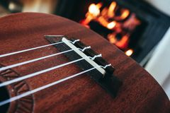 Ukulele small guitar close up stings, fireplace on the background. Musical concept, guitar fret board macro, fire in chimney, cos. Y romantic atmosphere stock images
