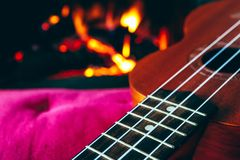 Ukulele small guitar close up stings, fireplace on the background. Musical concept, guitar fret board macro, fire in chimney, cos. Y romantic atmosphere stock photo