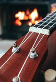 Ukulele small guitar close up stings, fireplace on the background. Musical concept, guitar fret board macro, fire in chimney, cos. Y romantic atmosphere royalty free stock images
