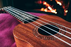 Ukulele small guitar close up stings, fireplace on the background. Musical concept, guitar fret board macro, fire in chimney, cos. Y romantic atmosphere royalty free stock photo
