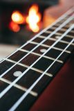 Ukulele small guitar close up stings, fireplace on the background. Musical concept, guitar fret board macro, fire in chimney, cos. Y romantic atmosphere royalty free stock photos