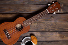 Ukulele ukulele with cup of coffee and croissant. On wooden background royalty free stock photo