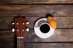 Ukulele ukulele with cup of coffee and croissant. On wooden background royalty free stock photography