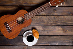 Ukulele ukulele with cup of coffee and croissant. On wooden background stock photography