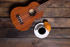 Ukulele ukulele with cup of coffee and croissant. On wooden background stock photos