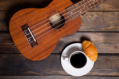 Ukulele ukulele with cup of coffee and croissant. On wooden background royalty free stock photos