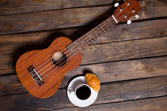 Ukulele ukulele with cup of coffee and croissant. On wooden background royalty free stock images