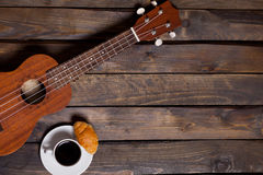 Ukulele ukulele with cup of coffee and croissant. On wooden background royalty free stock image