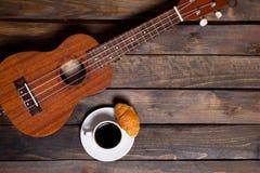 Ukulele ukulele z filiżanką kawy i croissant Fotografia Stock