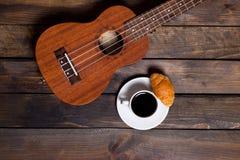 Ukulele ukulele z filiżanką kawy i croissant Zdjęcia Stock