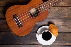 Ukulele ukulele z filiżanką kawy i croissant Zdjęcia Royalty Free