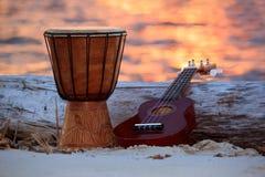 Ukulele und ethnische Trommel auf einem Strand lizenzfreies stockfoto