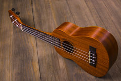 Ukulele in vintage wood background. Little four-string Hawaiian Guitar, on a dark wooden background Royalty Free Stock Images