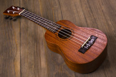 Ukulele in vintage wood background. Little four-string Hawaiian Guitar, on a dark wooden background Royalty Free Stock Photos
