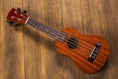 Ukulele in vintage wood background. Little four-string Hawaiian Guitar, on a dark wooden background Stock Photo