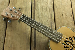 Ukulele, which rests on a wooden table. Stock Photos