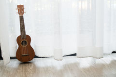 Ukulele on white drape background. Royalty Free Stock Image