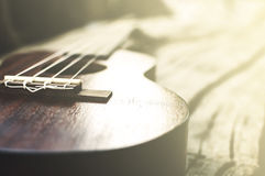 Ukulele on wood. Close-up ukulele on wood background. over light Stock Images
